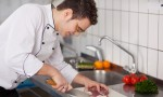 Koch schneidet in einer Küche Fleisch