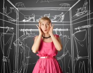 Junge Frau im rosa Kleid überlegt was sie anziehen soll.