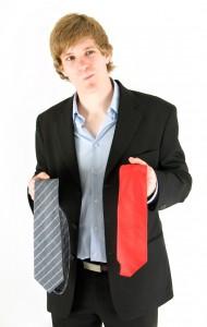 Junge Mann hält zwei Krawatten in der Hand und überlegt, welche die passende ist