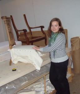 Junge Frau arbeitet an einem Tisch und restauriert einen alten Stuhl