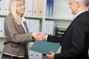 Blonde junge Frau schüttelt nach einem Vorstellungsgespräch älteren Mann mit Brille die Hand.