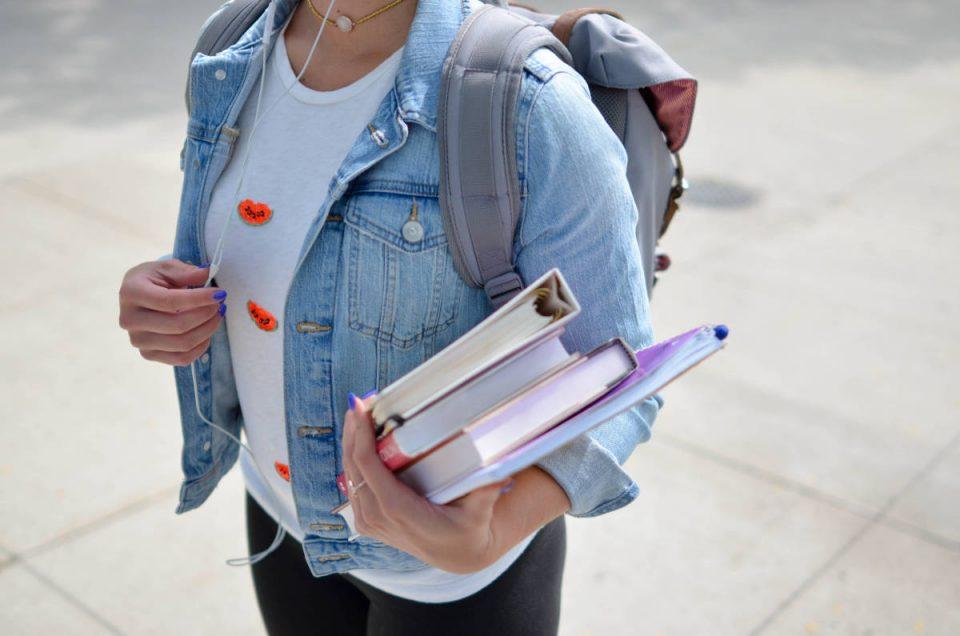 Frau trägt Rucksack und Bücher im Arm
