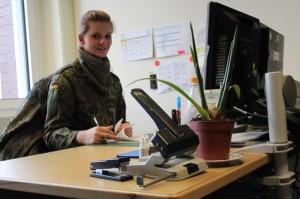 Soldatin in Uniform am Schreibtisch