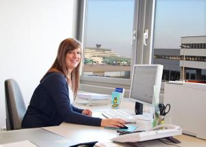 Auszubildende sitzt am Schreibtisch , im Hintergrund der Flughafen Köln Bonn