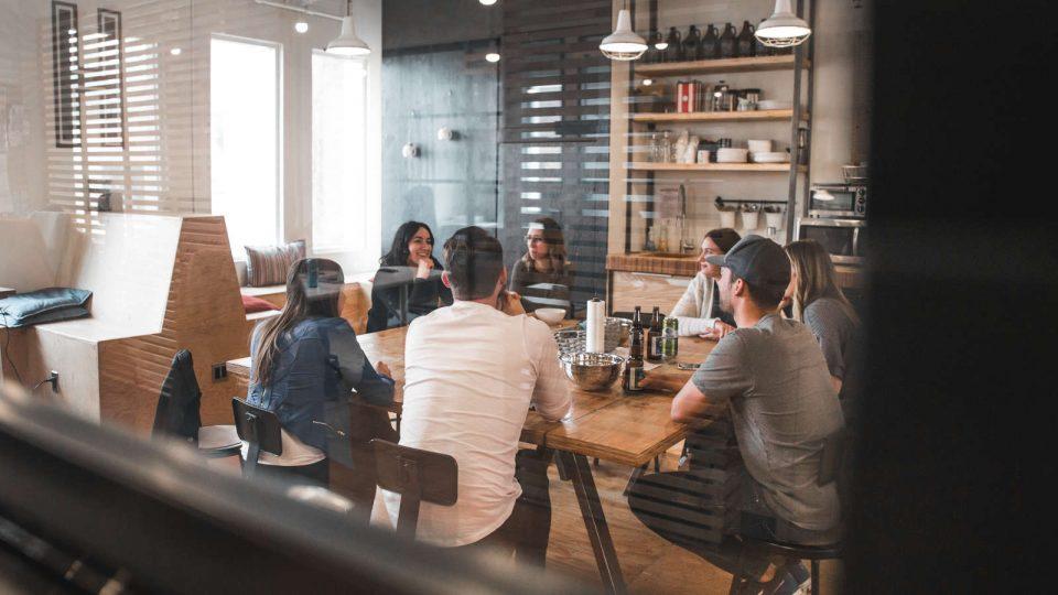 Junge Menschen sitzen zusammen am Tisch