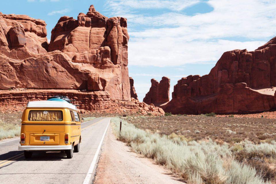 Gelber VW Bus fährt auf Straße zwischen Bergen