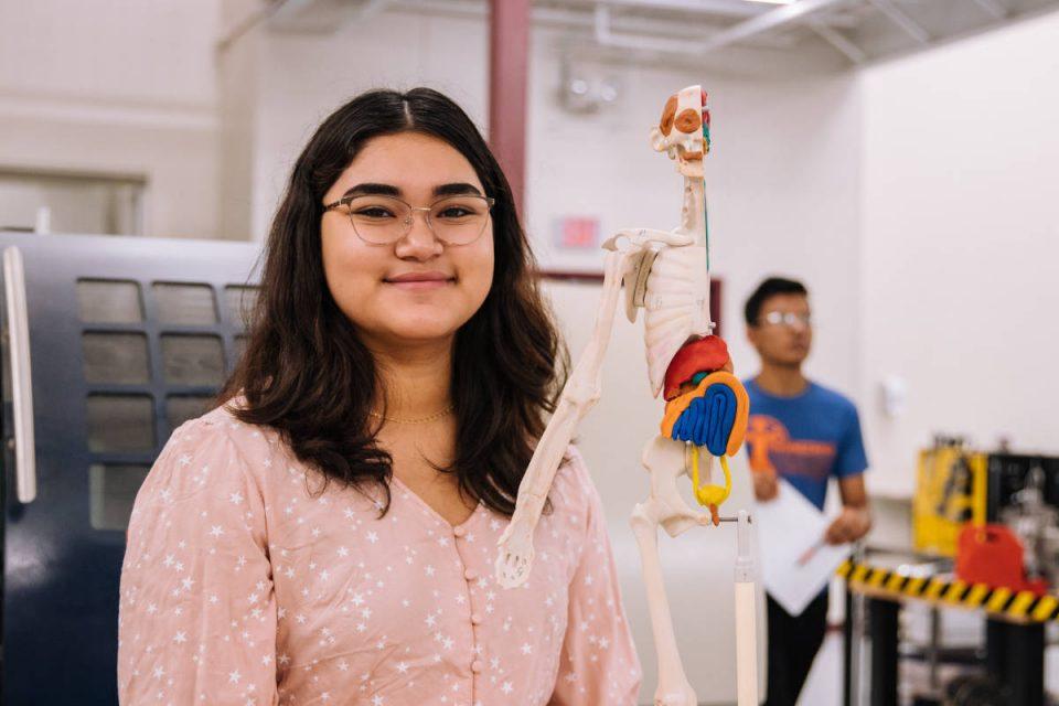 Mädchen lächelt in die Kamera während sie im Klassenraum sitzt