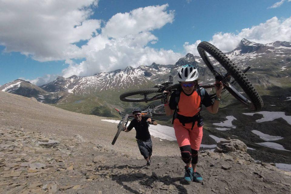 Frau und Mann tragen Mountainbike den Berg hoch