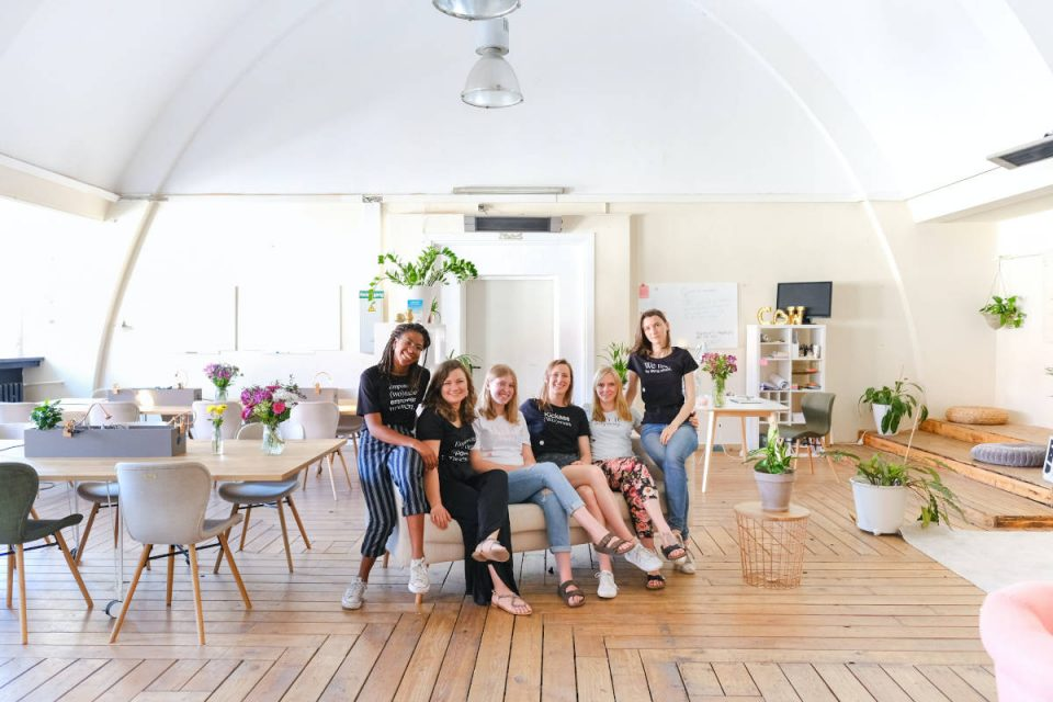 Sechs Frauen sitzen in hellem Büro