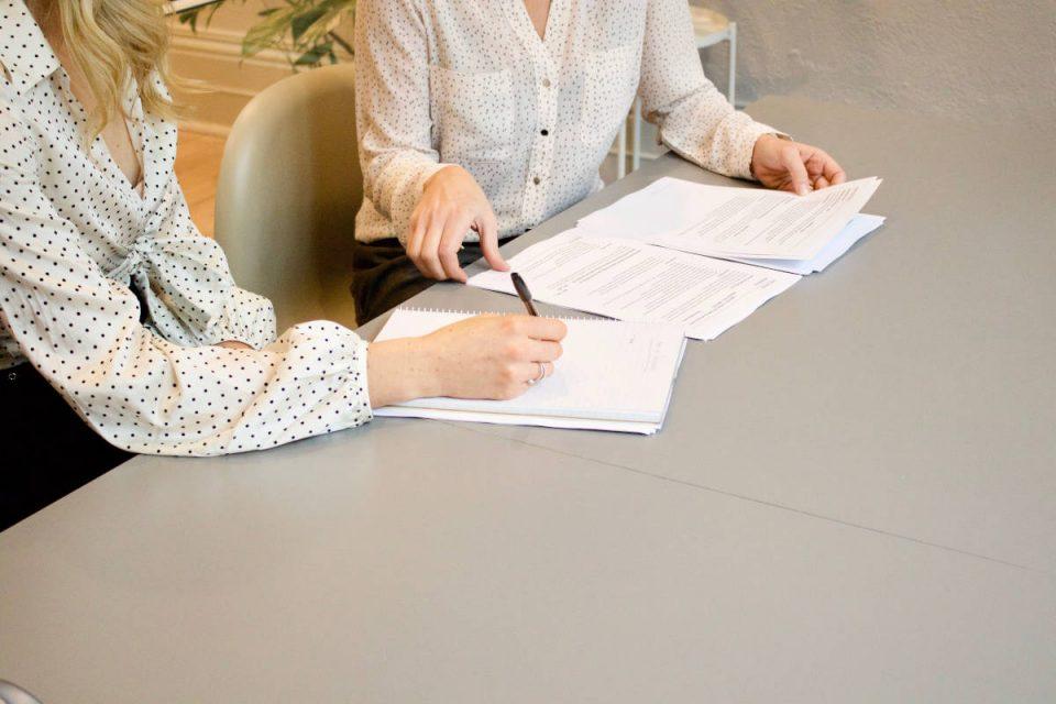 2 Frauen mit hellen Blusen sitzen an grauem Tisch und lehnen sich über Papiere