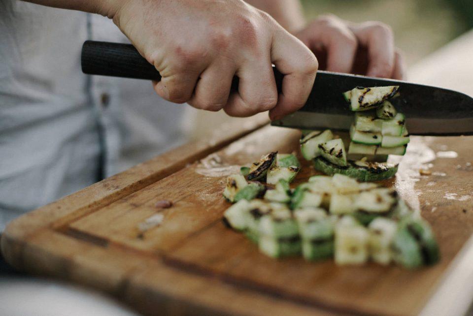 Koch schneidet Zucchini auf Holzbrett