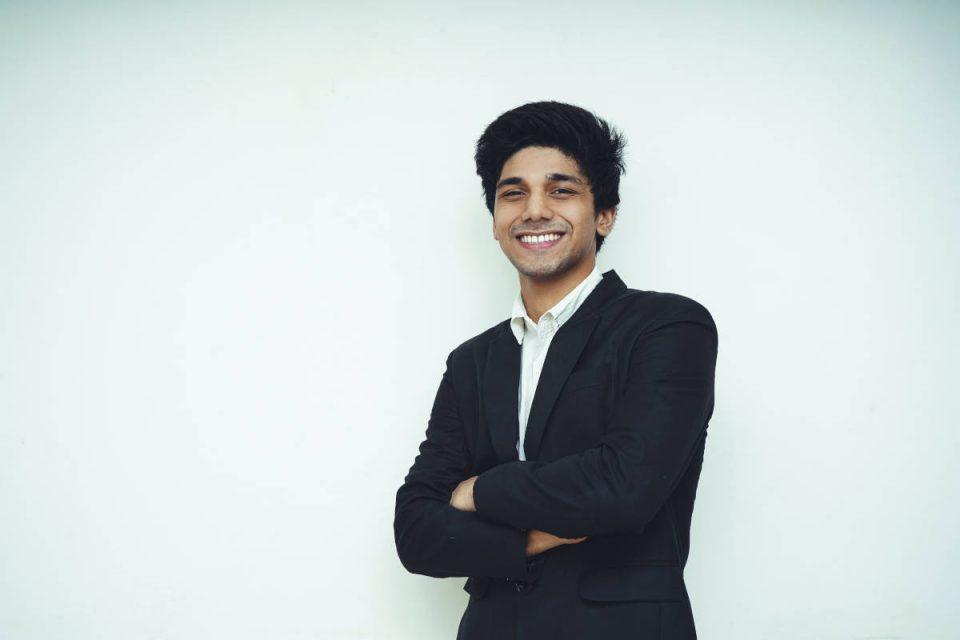 Junger Mann steht vor weißem Hintergrund mit verschränkten Armen, trägt schwarzen Anzug und lächelt