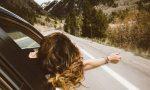 Frau lehnt sich aus fahrendem Auto