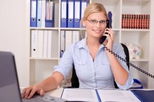 Attraktive Blondine telefoniert im Büro