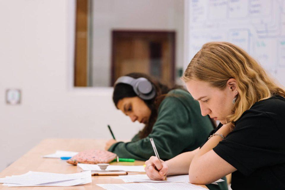 Zwei junge Menschen sitzen am Tisch und schreiben