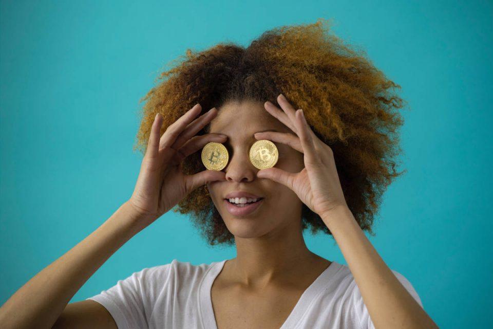 Frau steht vor türkisem Hintergrund und hält sich Goldmünzen vor die Augen