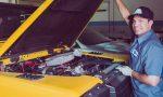 Mann steht vor geöffneter Motorhaube von gelben Auto