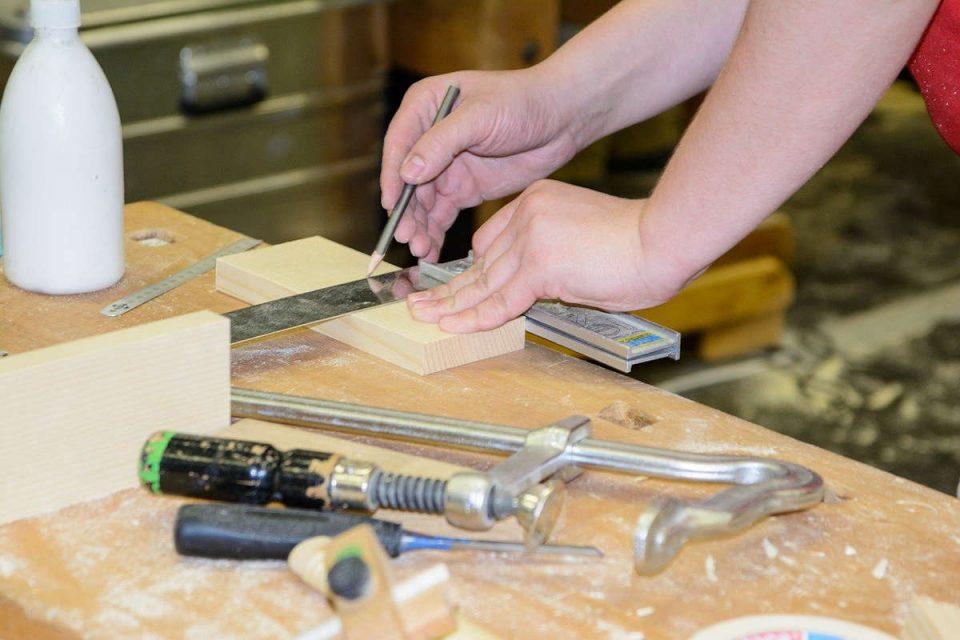 Auszubildener handwerkt an einem Tisch